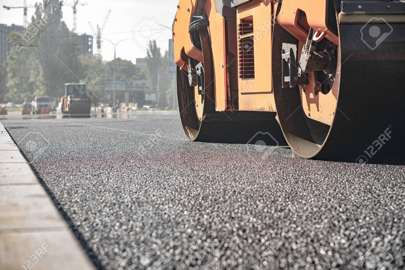 steamroller compact flatten out the asphalt tar - 153899761
