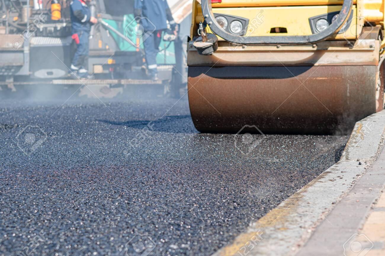 steamroller compact flatten out the asphalt tar - 153899773
