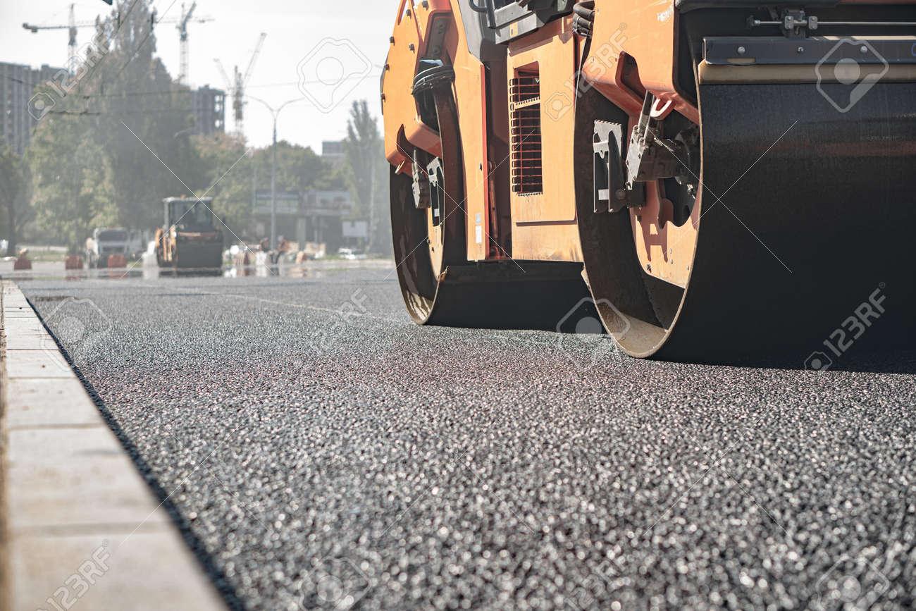 steamroller compact flatten out the asphalt tar - 154775784