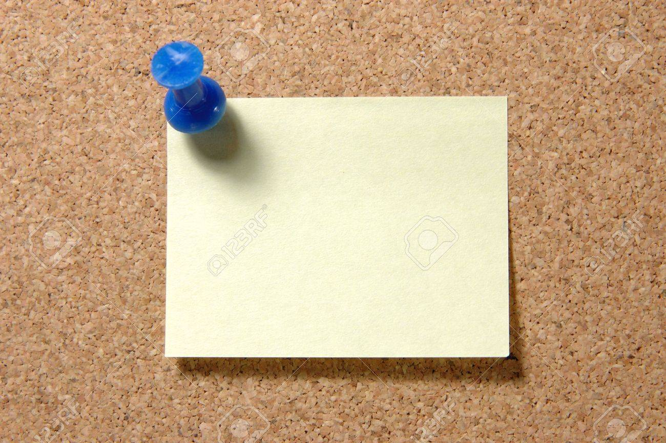 Yellow post-it note with blue pushpin on corkboard Stock Photo - 601052