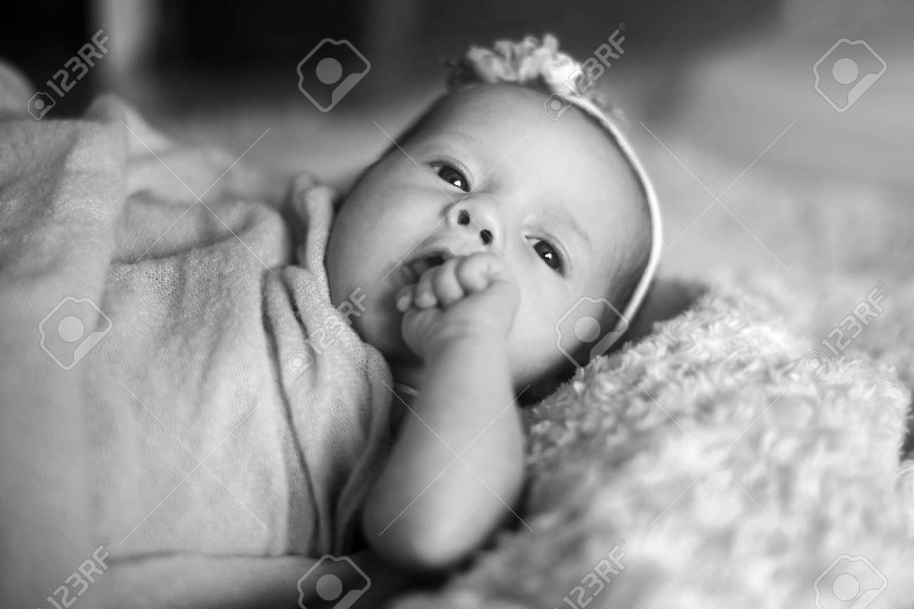 Cute newborn baby girl in the bed black and white stock photo 75228382