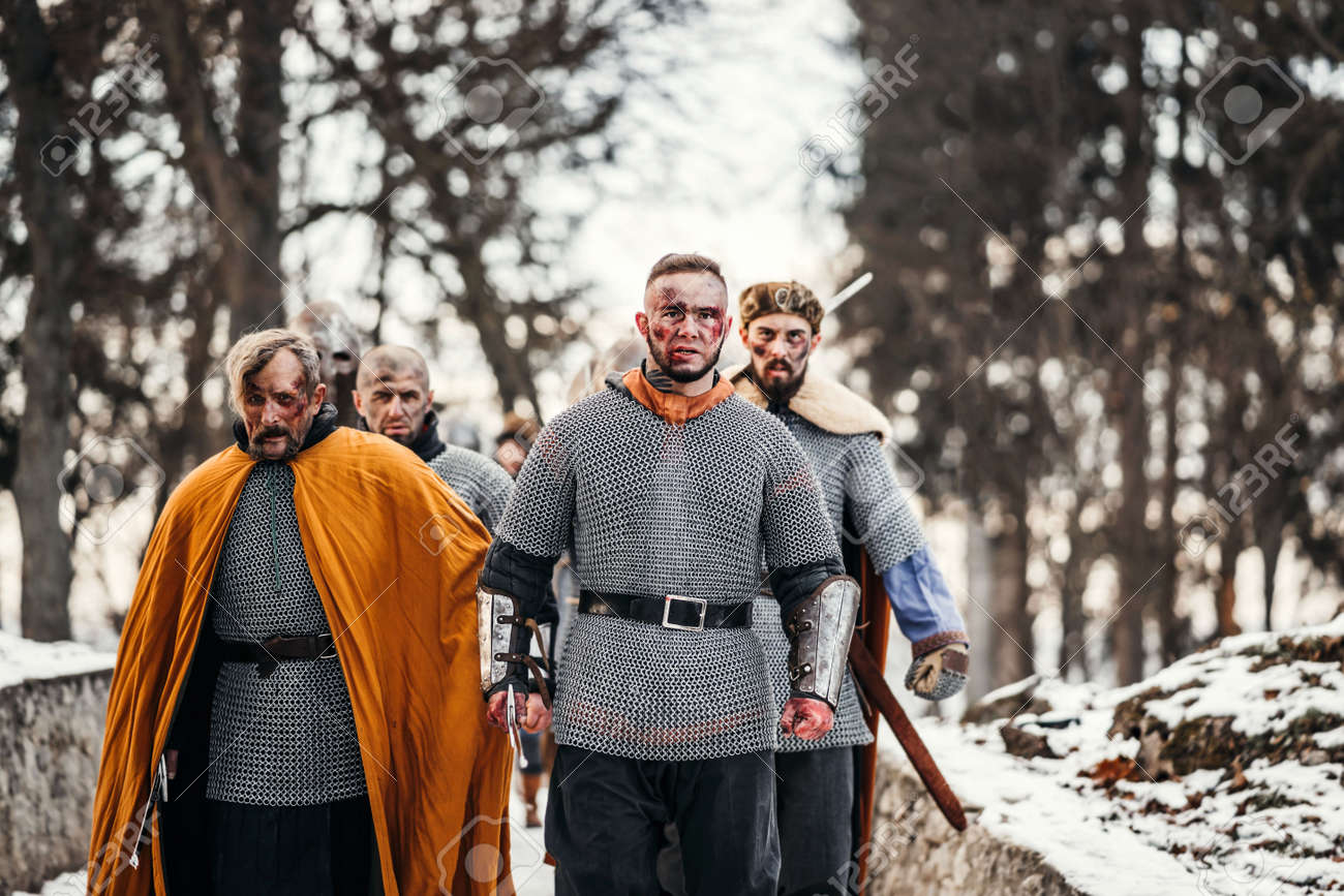 Photo of knights in armor with swords during the war. Evil emotions of a warrior who goes to battle with the sword. - 150875046