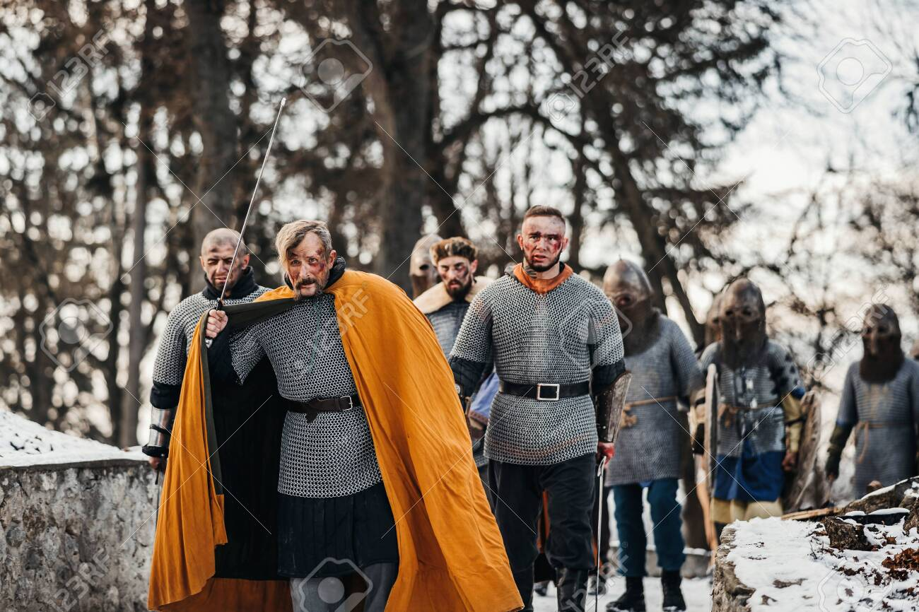 Photo of knights in armor with swords during the war. Evil emotions of a warrior who goes to battle with the sword. - 150875231