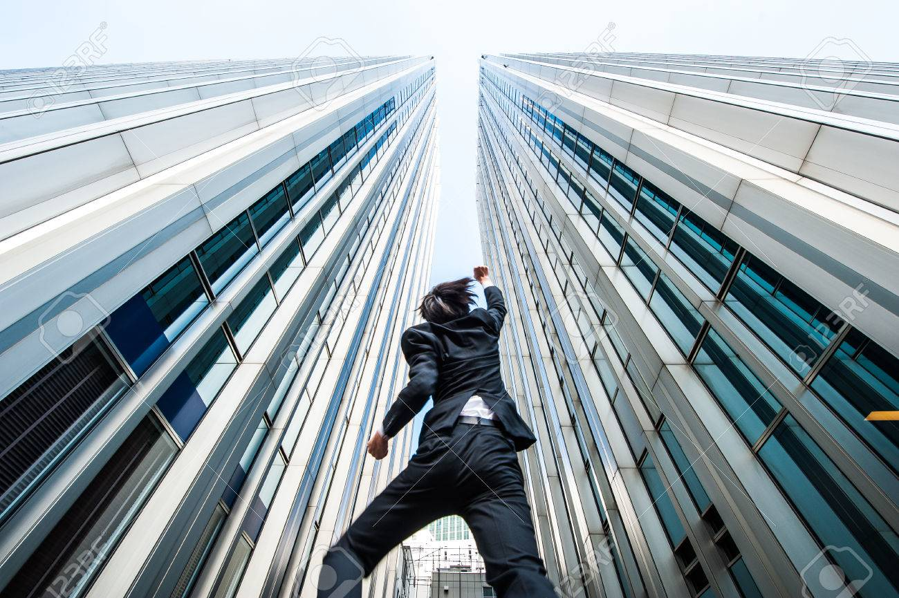 businessman jumping over the camera low angle building background