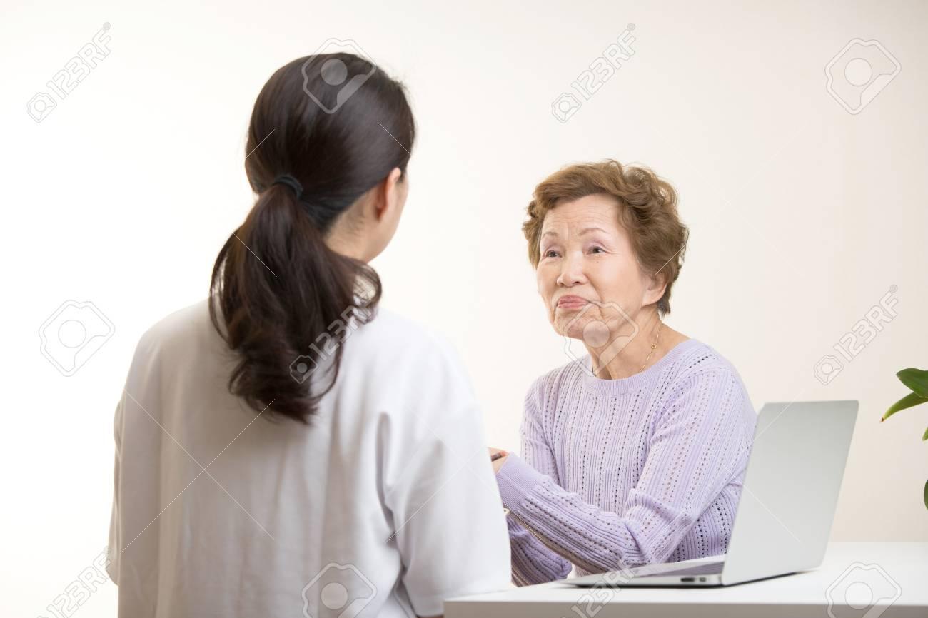 Asian elderly women talking to a doctor - 103464754