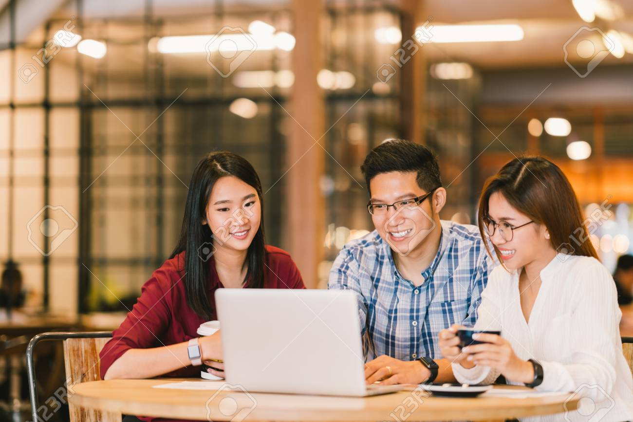 Young Asian college students group or coworkers using laptop computer together at cafe or university. Casual business, freelance work, coffee break meeting, e-learning or e-commerce activity concept - 93480356
