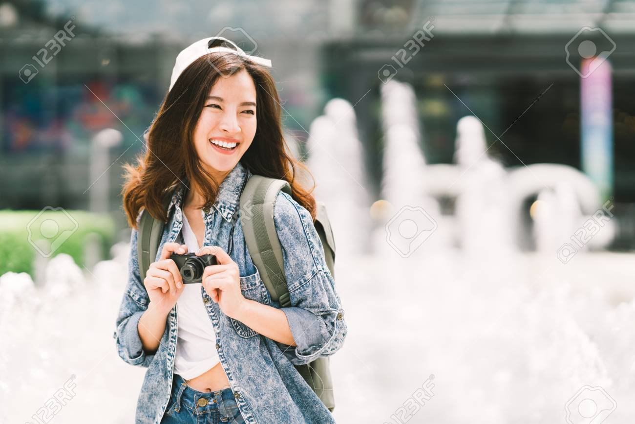 Young beautiful Asian backpack traveler woman using digital compact camera and smile, looking at copy space. Journey trip lifestyle, world travel explorer or Asia summer tourism concept - 103426777