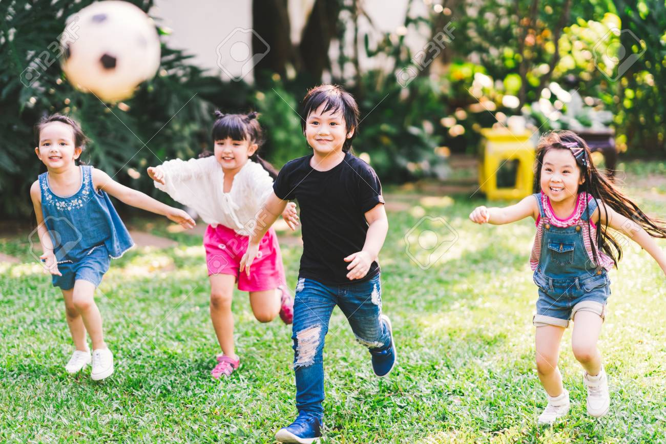 Asian and mixed race happy young kids running playing football together in garden. Multi-ethnic children group, outdoor sport exercising, leisure game activity, or childhood fun lifestyle concept - 121192810
