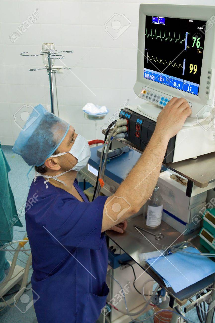 anesthesiologist with medical monitor in operation room - 10622253