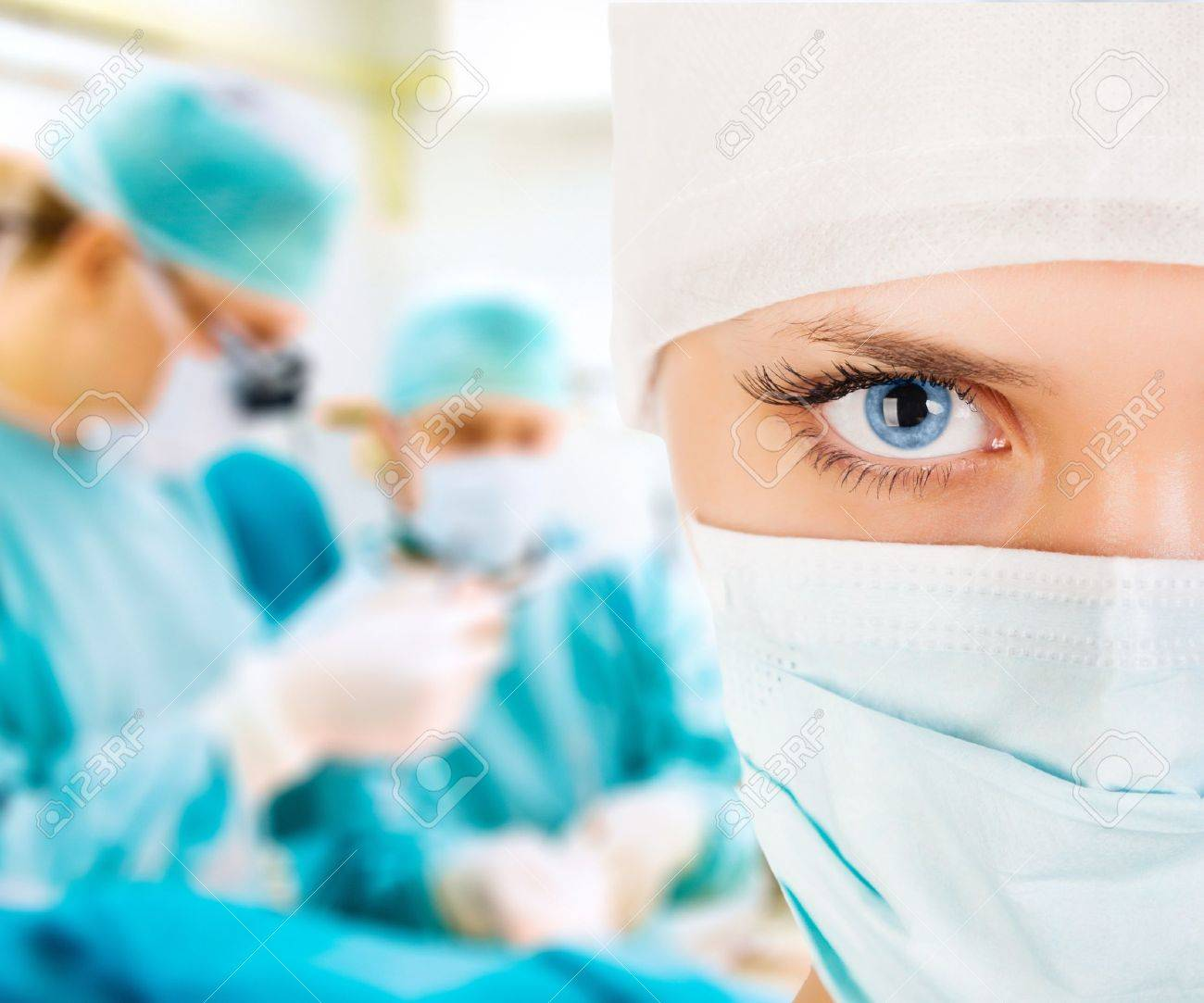 Close-up of a female surgeon with his team in operation room - 19383927