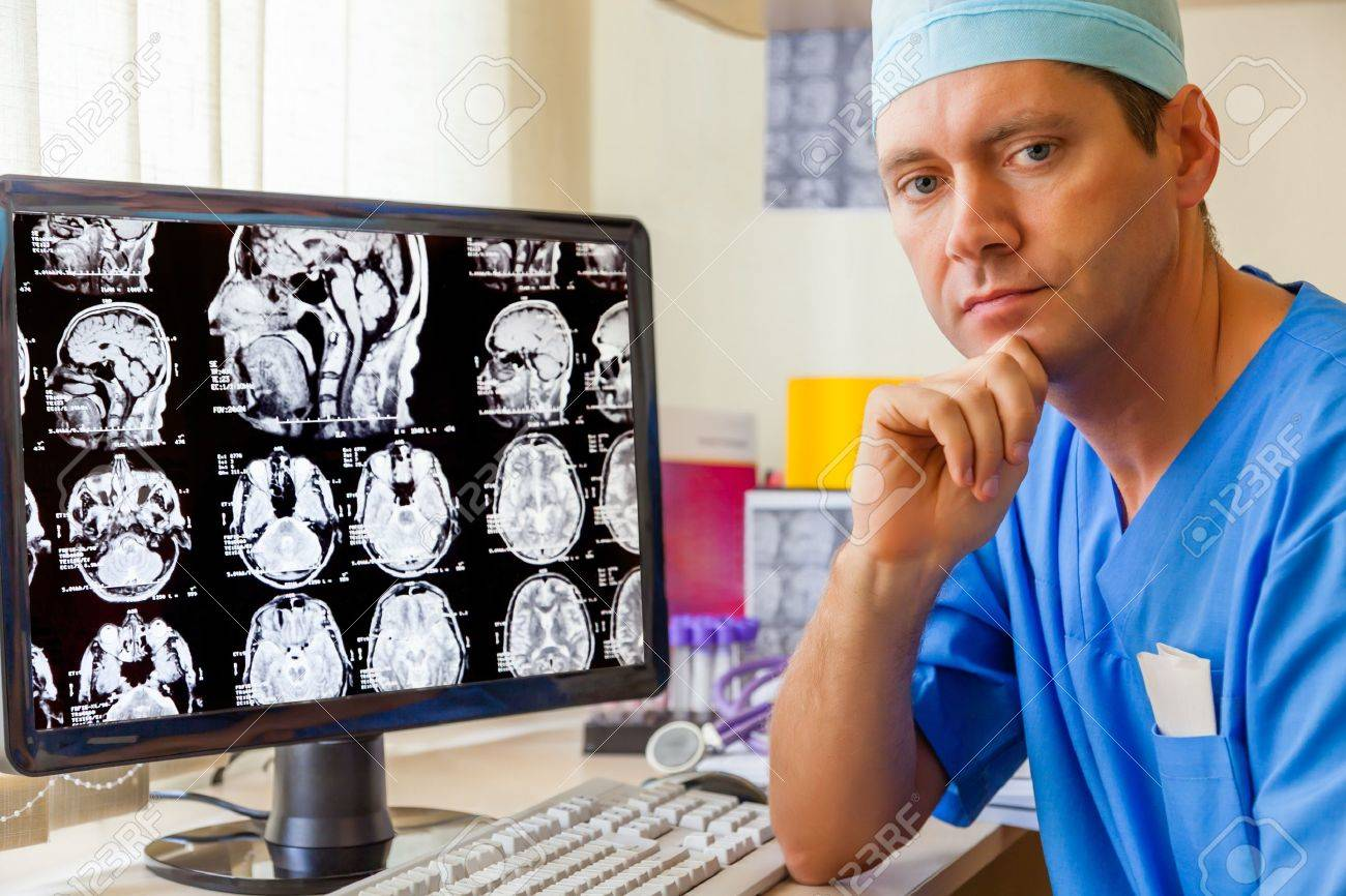 Experienced doctor with an MRI scan of the Brain on Monitior - 19537157