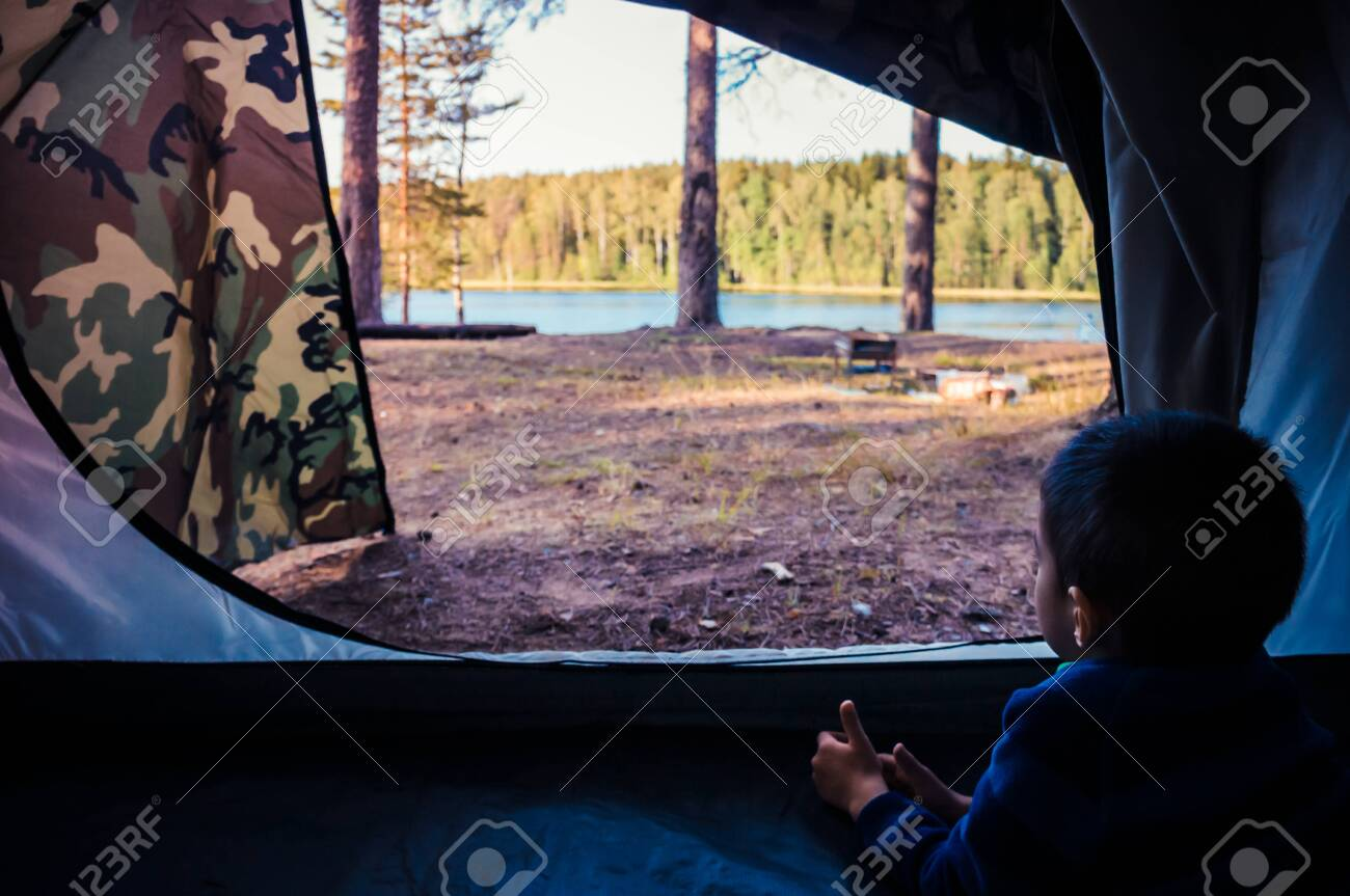 Little boy looking outside camping tent on the lake landscape - 149275232