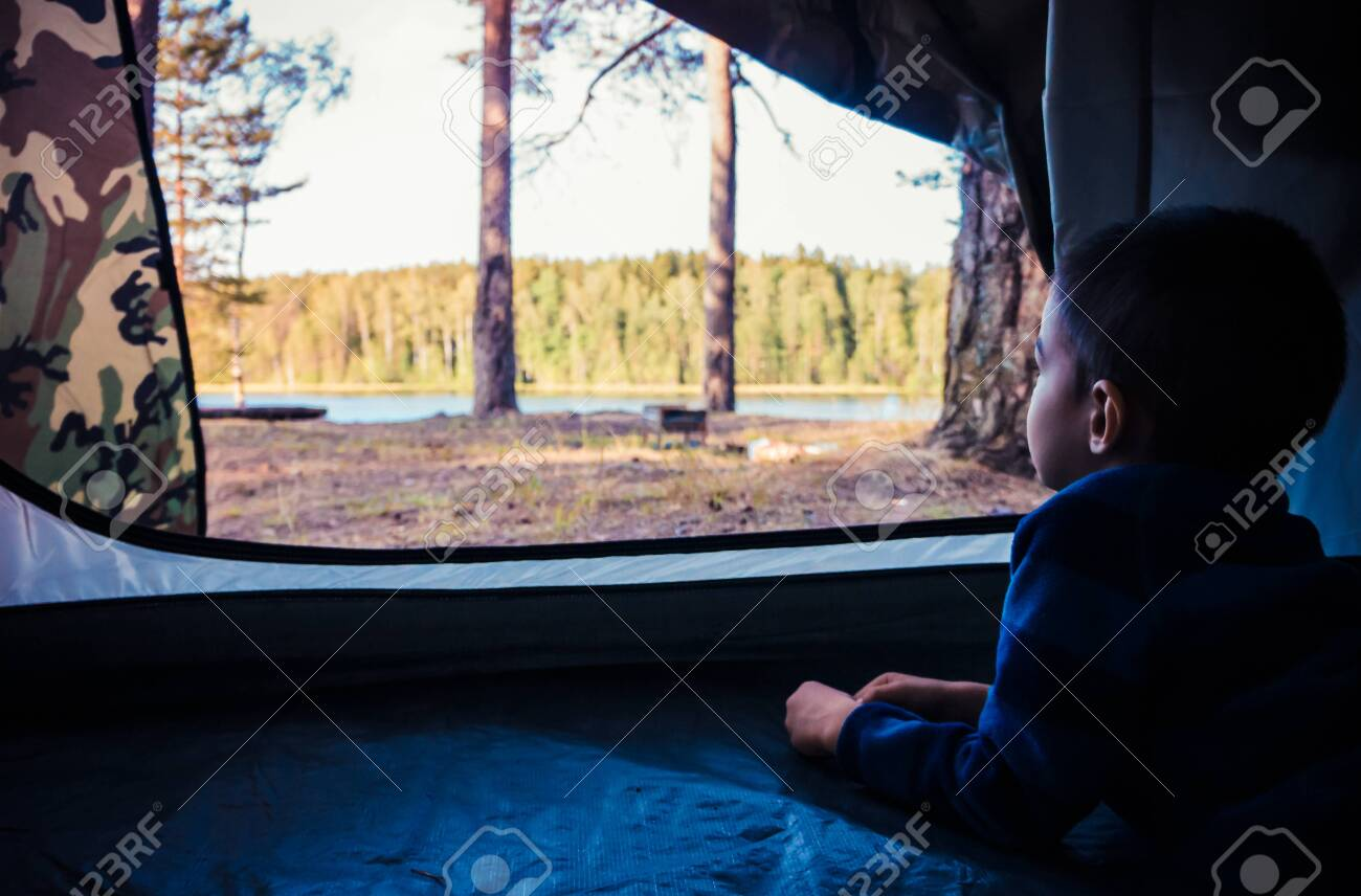 Little boy looking outside camping tent on the lake landscape - 149275752