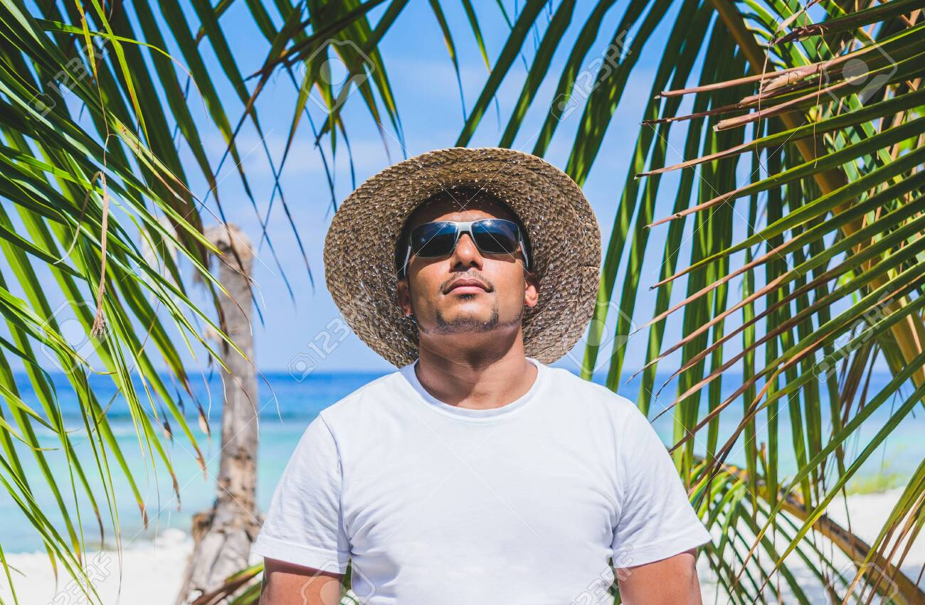 Portrait of young Indian man in sunglasses and straw hat at beach surrounded by palms - 150144179