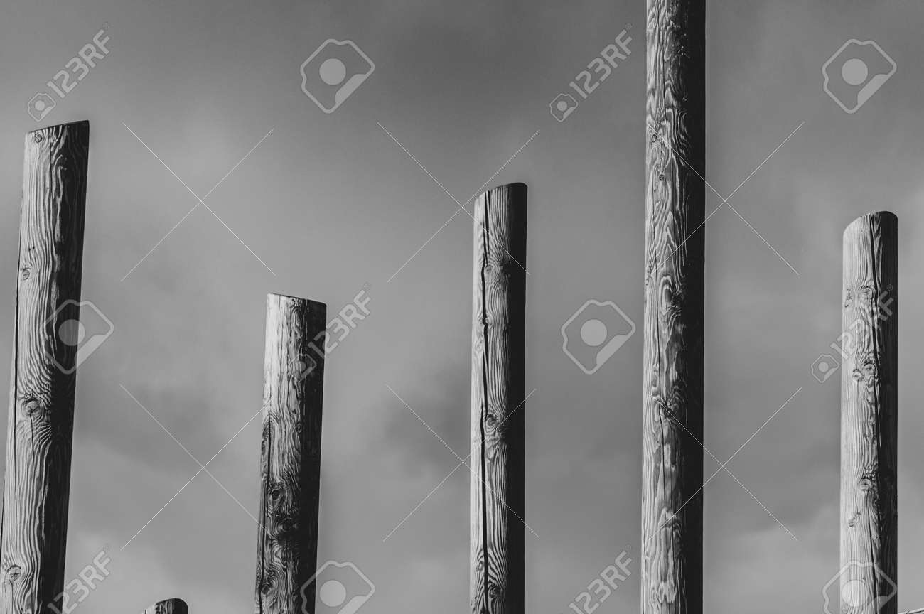 Abstract black and white pillars against cloudy sky - 164966358