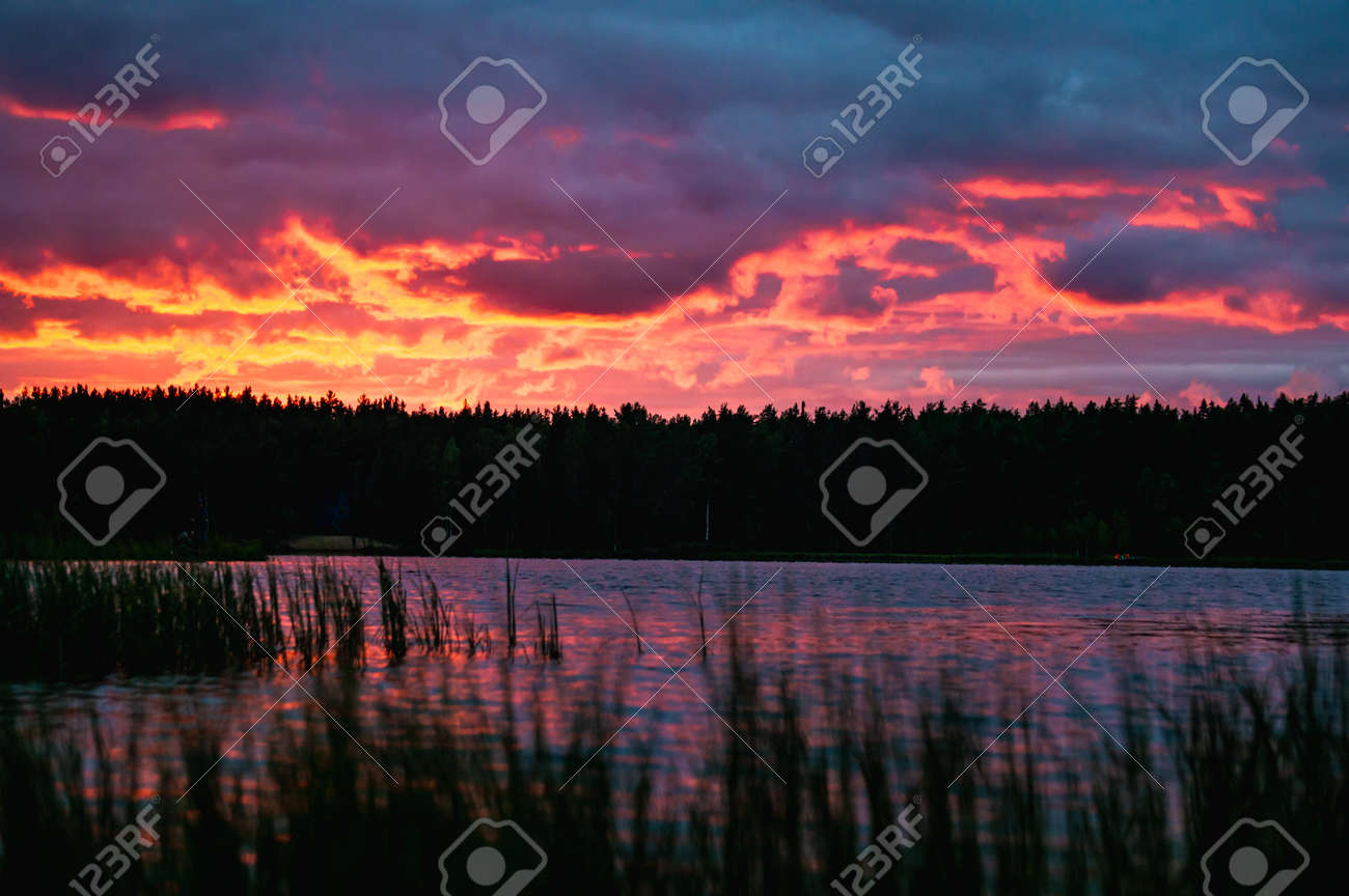 Red sunset with clouds over lake in forest in Russia - 164889455