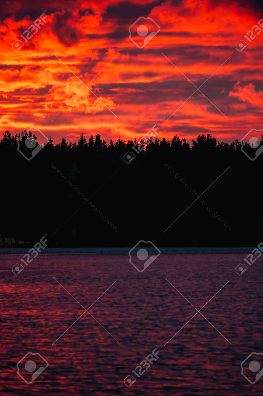 Red sunset with clouds over lake in forest in Russia - 164891649