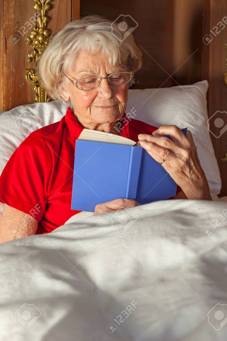 senior woman reading a hardcover book in bed sitting up against the pillows under her duvet