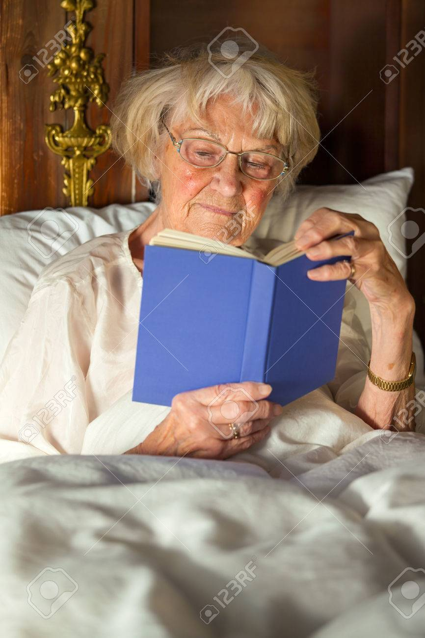 Elderly Woman In Her Nightgown Wearing Glasses Sitting Propped Up Against  The Pillows Reading A Hardcover