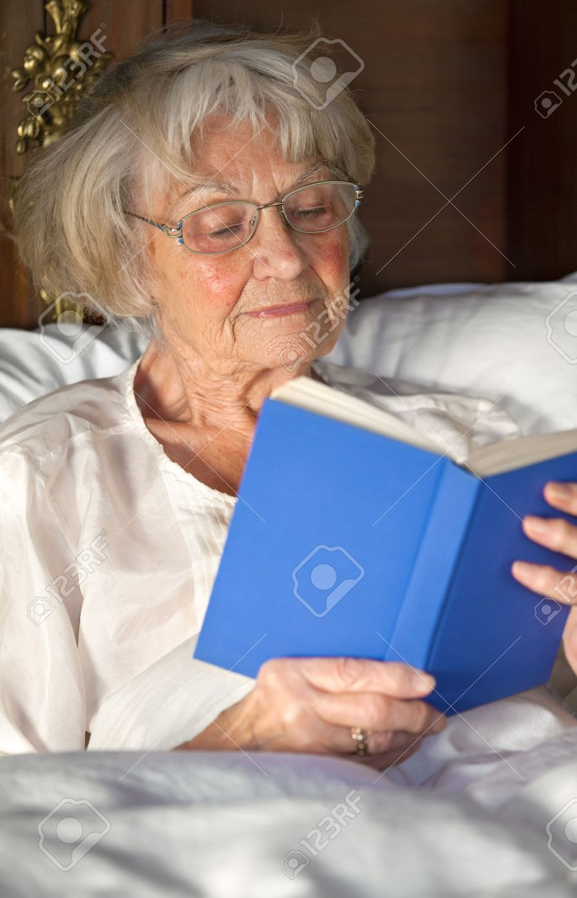 Elderly Female Pensioner Wearing Glasses Reading A Book In Bed Sitting  Propped Upfortably Against Her
