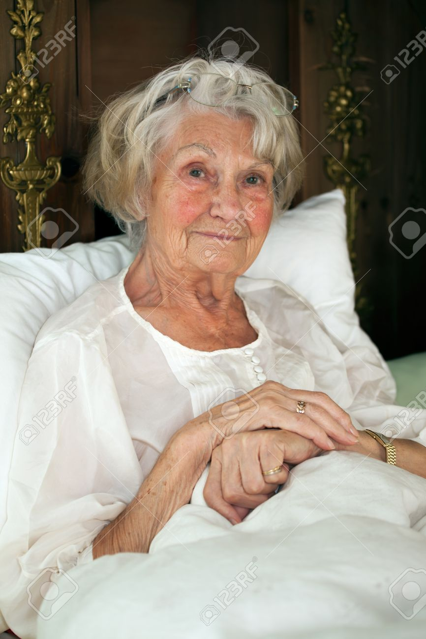 Senior Woman Resting In Bed Sitting Propped Up Against The Pillows In Her  Nightgown Looking At