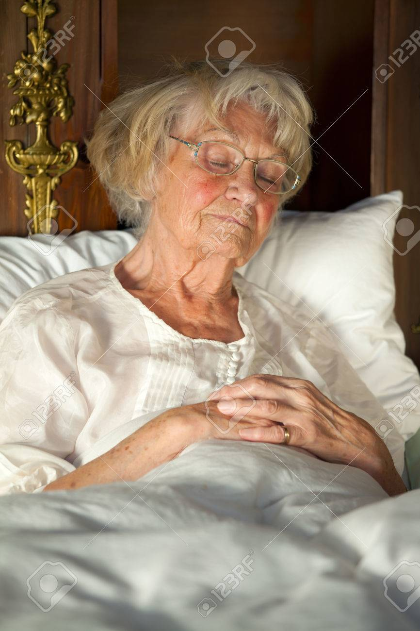 Elderly Lady Sitting Propped Up Against The Pillows In Her Nightgown And  Glasses Dozing In Her
