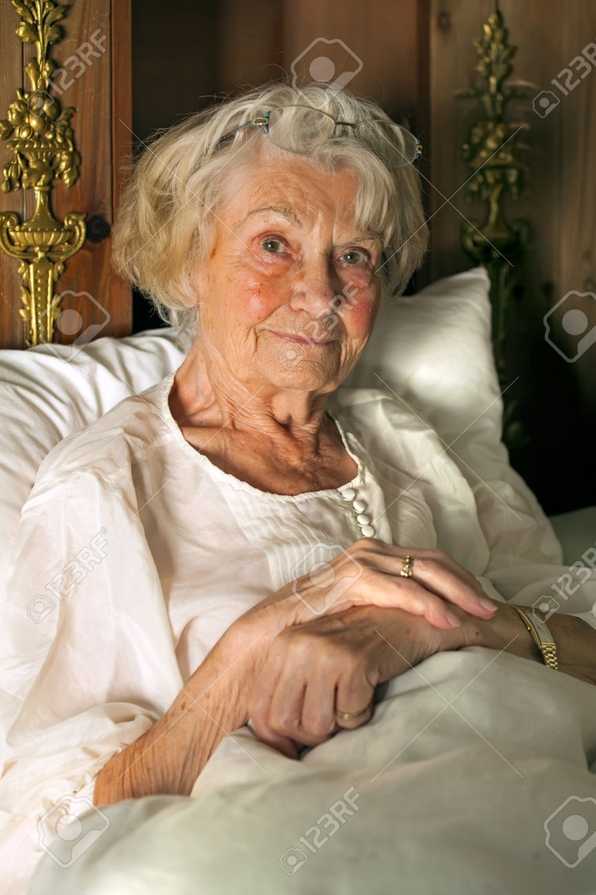 Senior Lady In Her Nightgown In Bed Sitting Propped Upfortably Against  Her Pillows Smiling At