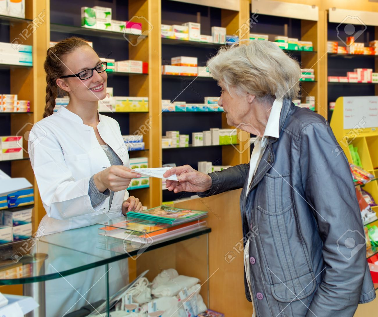 counter drugs images stock pictures royalty counter drugs counter drugs smiling attractive young female pharmacist serving a senior lady over the counter dispensing