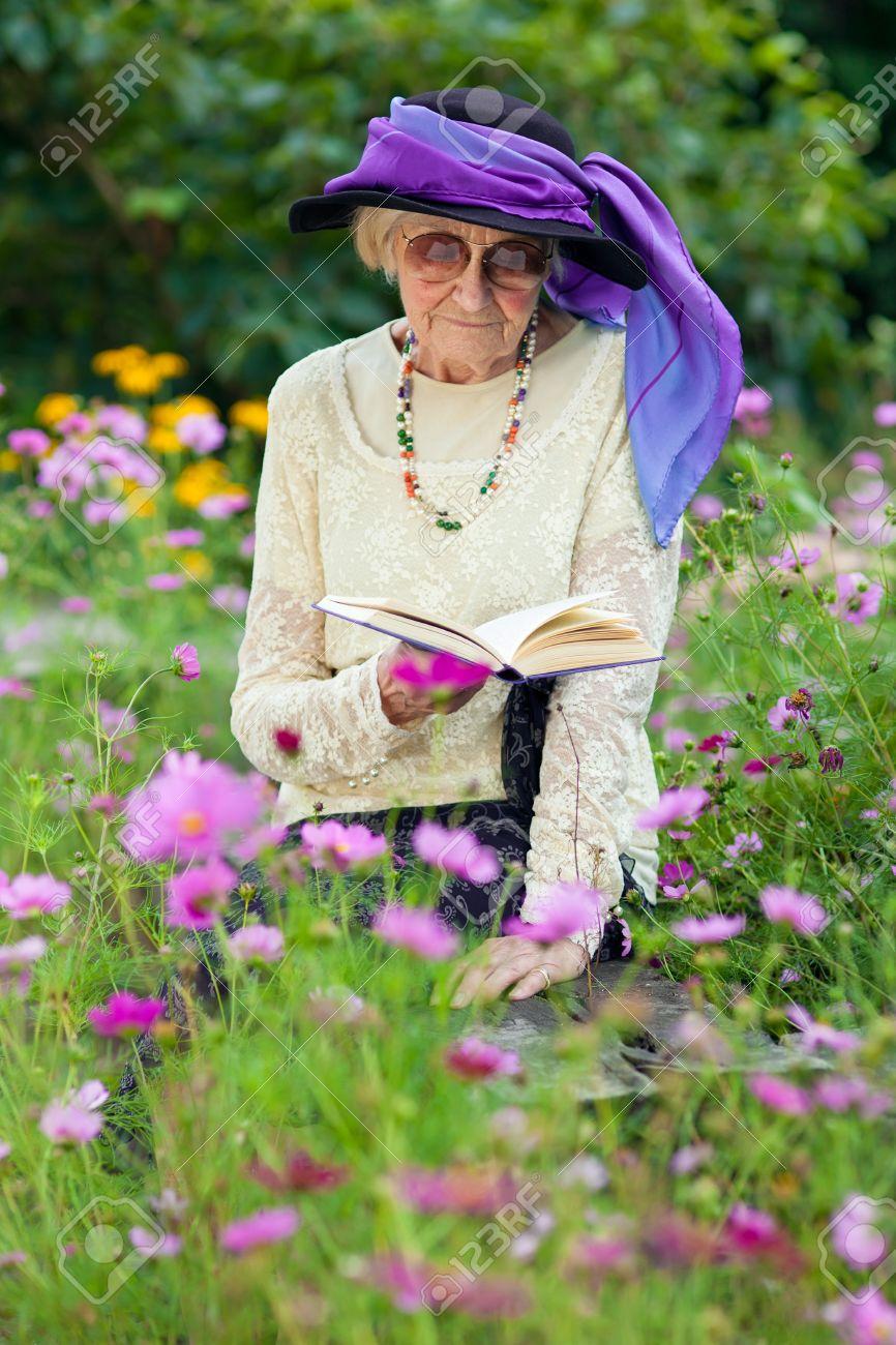 Elderly woman in a beautitul stylish purple hat sitting reading a stok fotoraf elderly woman in a beautitul stylish purple hat sitting reading a book on a wooden bench amongst pretty summer flowers in her garden mightylinksfo