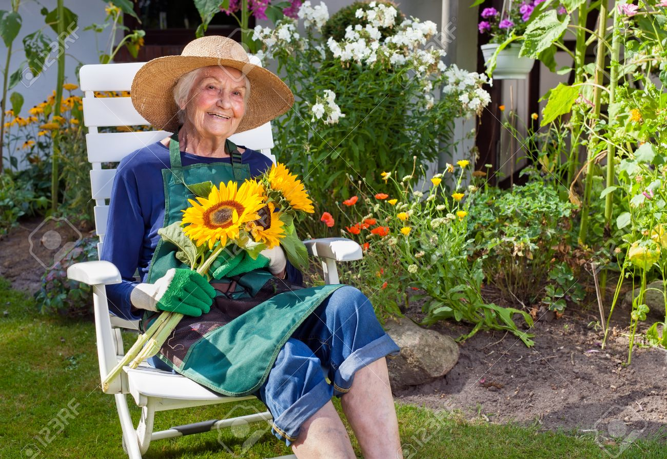 White apron and hat - Smiling Old Woman With Hat Apron And Gloves For Gardening Sitting On A White Chair