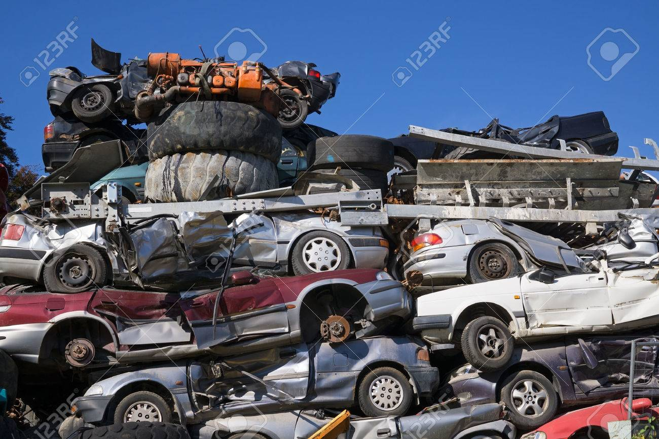 Low Angle View Of Old Squashed Cars Stacked At Junk Yard With ...