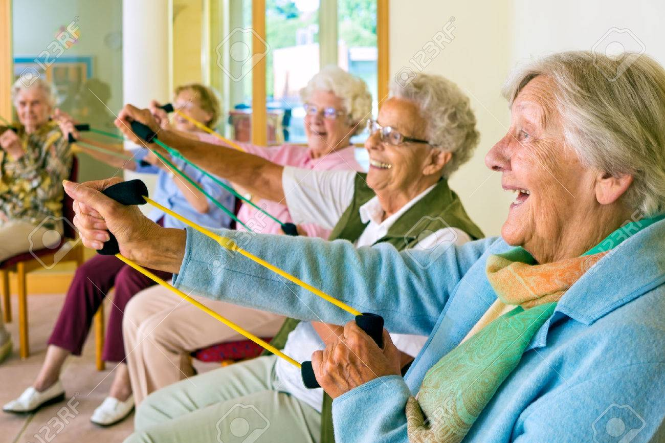 Large group of happy enthusiastic elderly ladies exercising in a gym sitting in chairs doing stretching exercises with rubber bands - 51471173