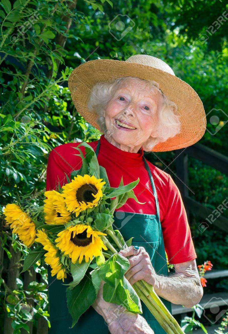 Señora Mayor Feliz Que Lleva Un Sombrero De Paja De Ala Ancha Y Delantal  Recogiendo Flores En Su Jardín De Pie Sonriendo A La Cámara Con Un Ramo De  ... 5ed432cbe0c