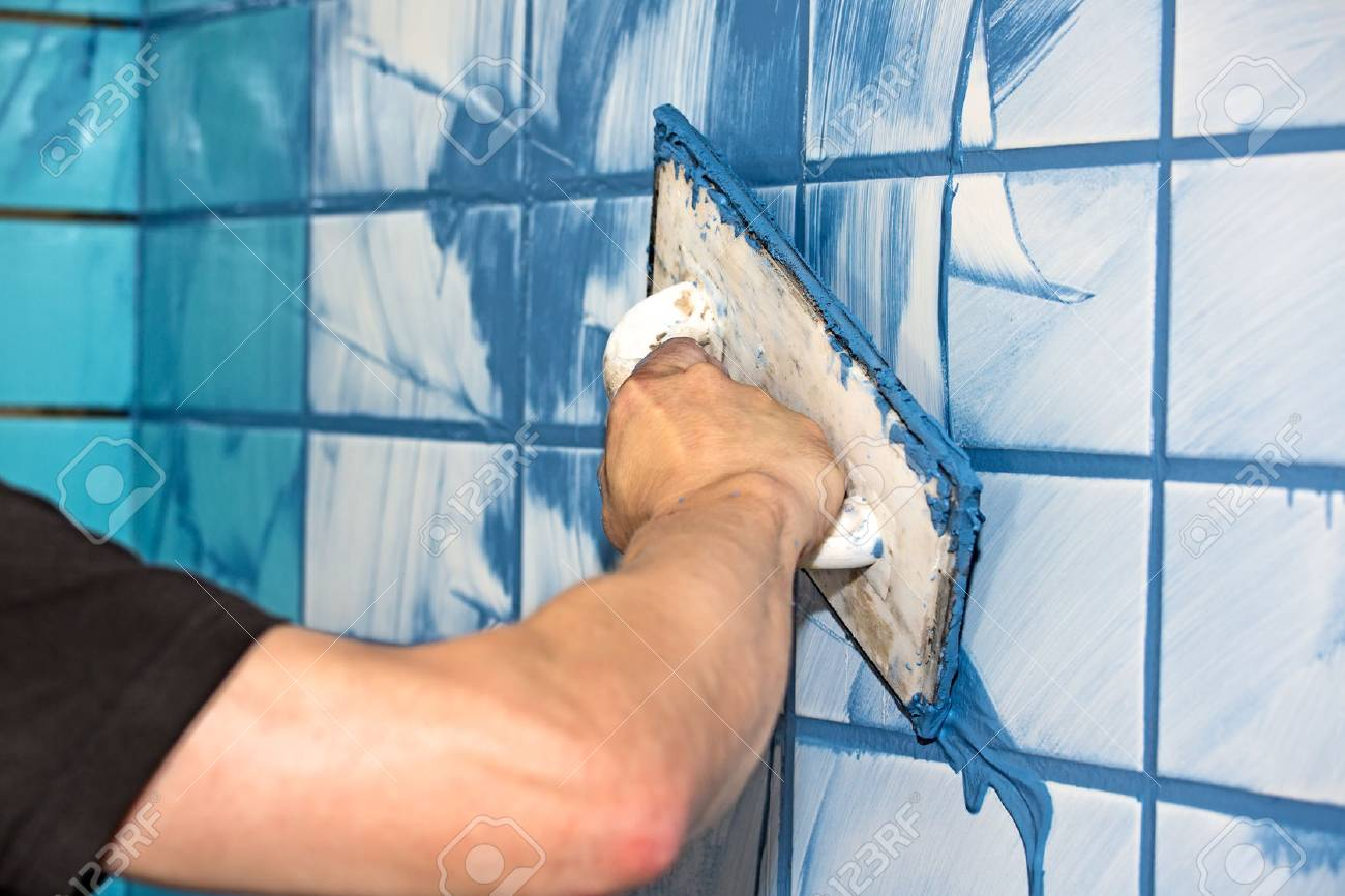 Workman Or Builder Applying Blue Grout To White Interior Tiles ...