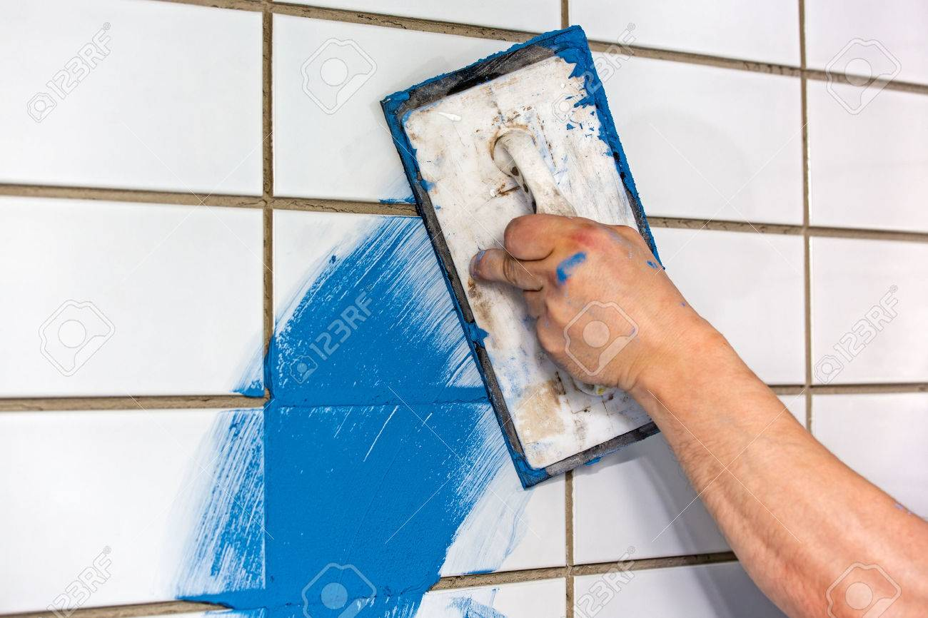 Builder Applying Colorful Blue Grouting To Newly Laid White Tiles ...