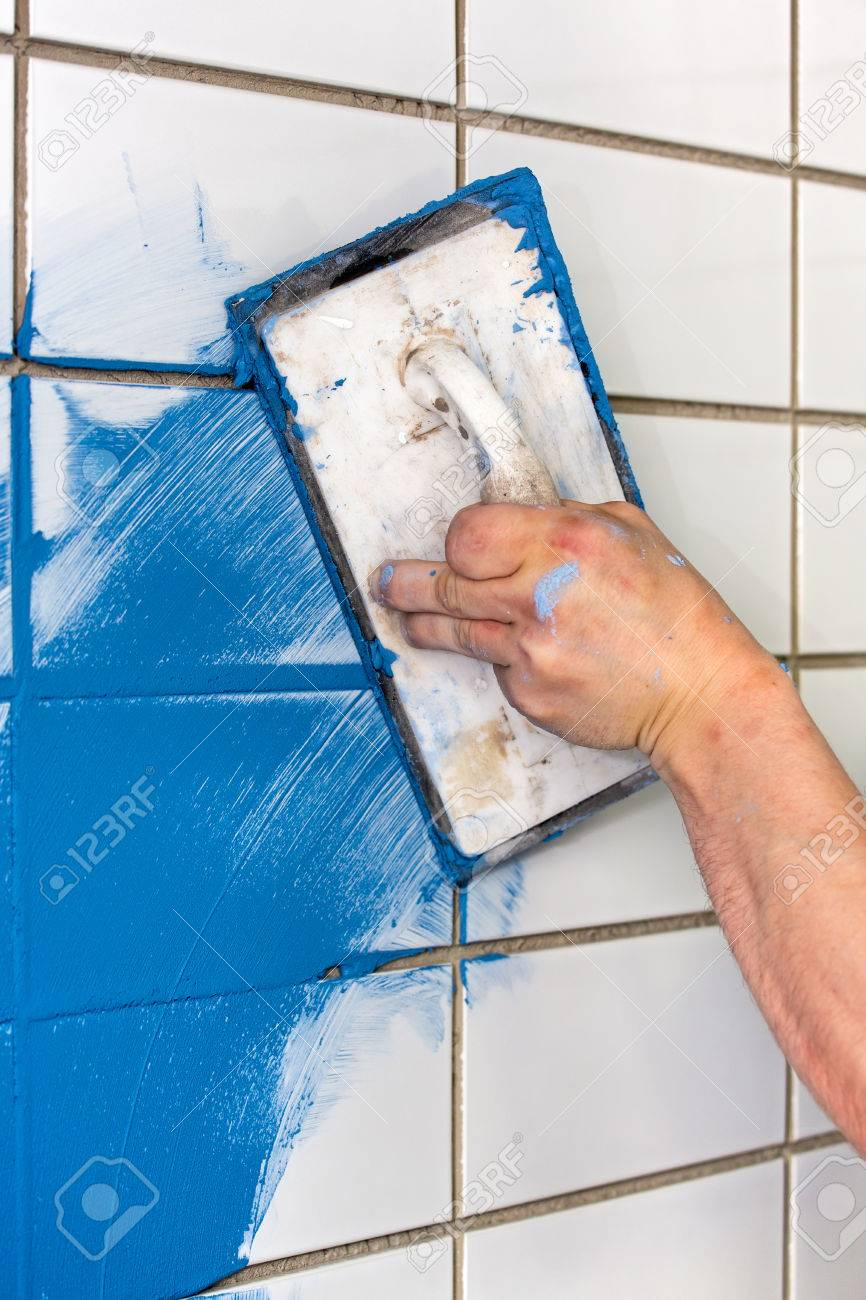 Workman Applying Blue Grout To White Tiles On A Wall Indoors.. Stock ...