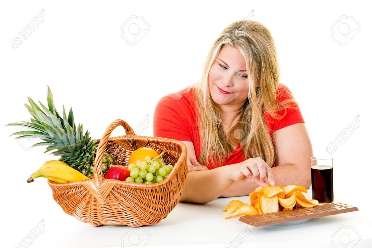 Woman blond woman choosing junk food over basket of healthy fruit on white. - 70370600