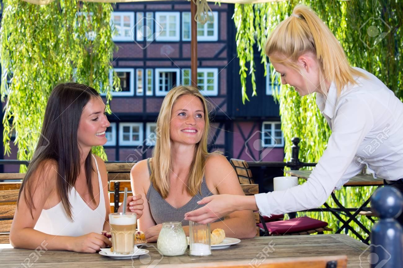 5bc41bd83fafce Standard-Bild - Weiblich Kellner junge hübsche Frauen Kunden mit Kaffee auf  der Straße Café Tisch sitzen und fröhlich lächelnd