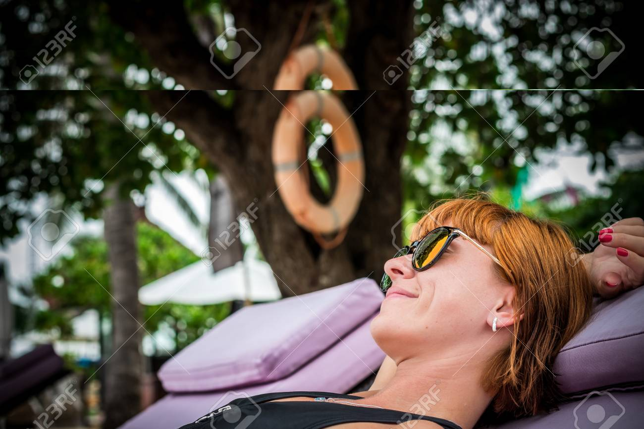 Fashion close up portrait of woman with sunglasses relaxing on deck chair.  Sexy summer day