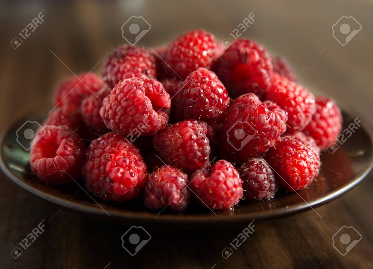 Fresh raspberries on brown plate, dark background, selective focus Stock Photo - 18574983