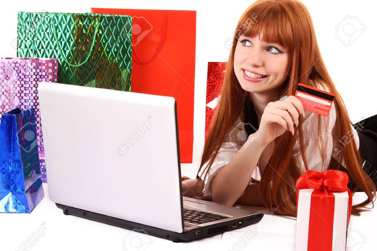 Beautiful, young, redhair woman with color  shopping bags shopping over internet.  On white background. Stock Photo - 6801855