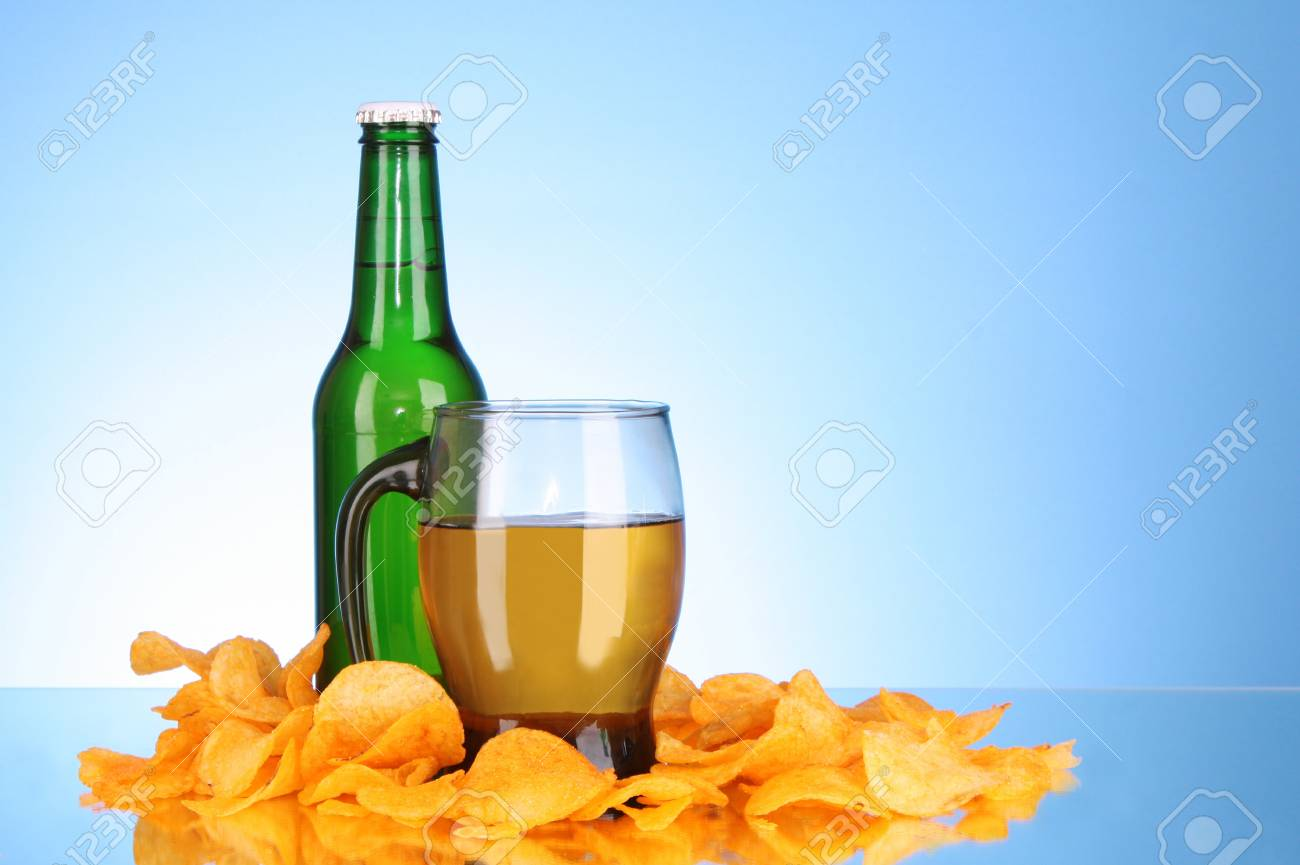 Bottles with beer, cup and potato chips on blue background Stock Photo - 8331506