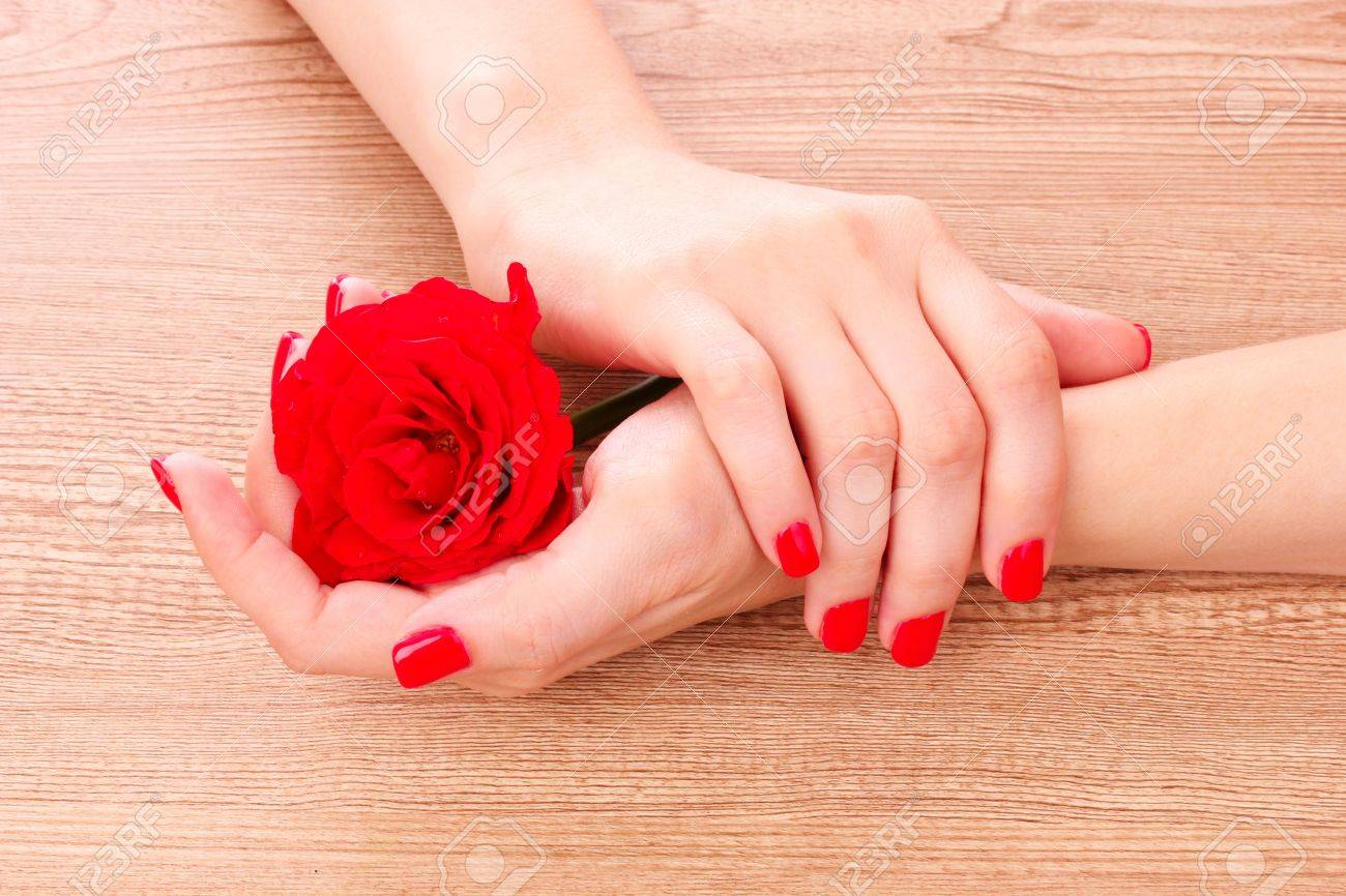beautiful red manicure and a flower on a wooden background Stock Photo - 9784888