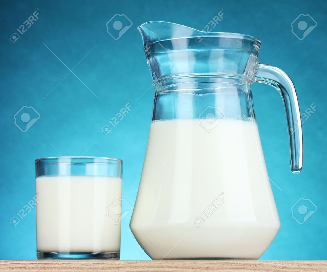 Tasty milk in jug and glass on blue background Stock Photo - 10518967