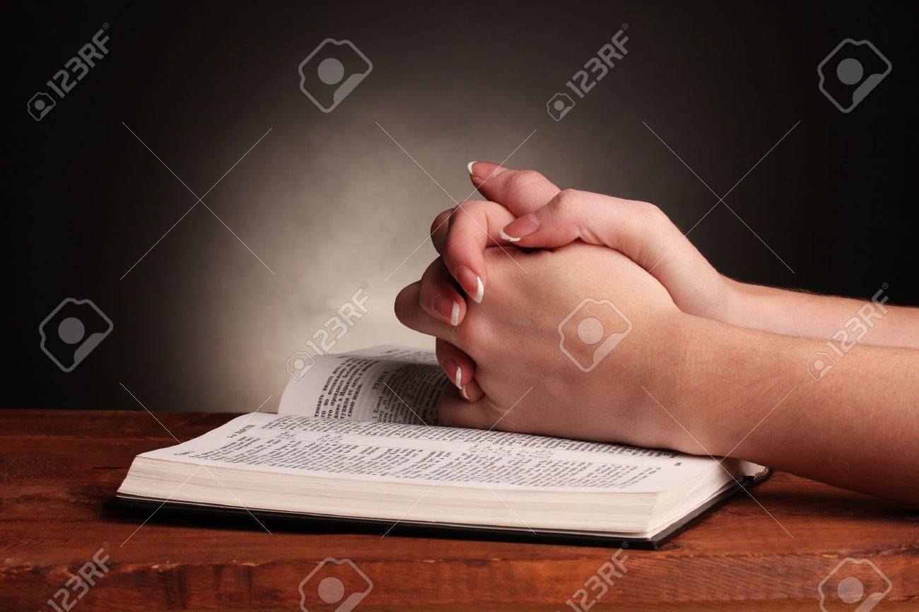 Hands folded in prayer over open russian Holy Bible on black background Stock Photo - 11169918