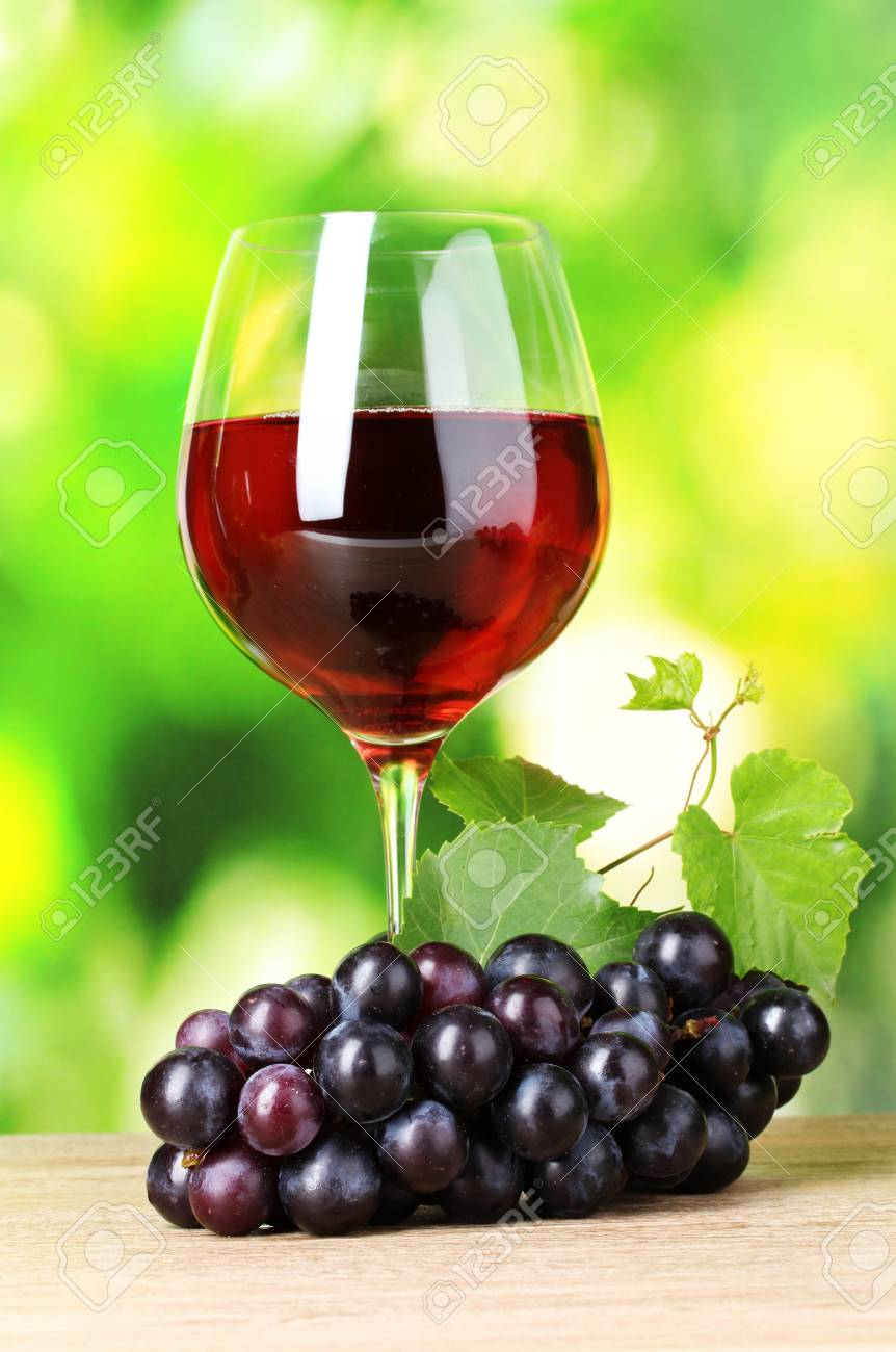 Ripe grapes and  glass of wine on  green background Stock Photo - 11220221