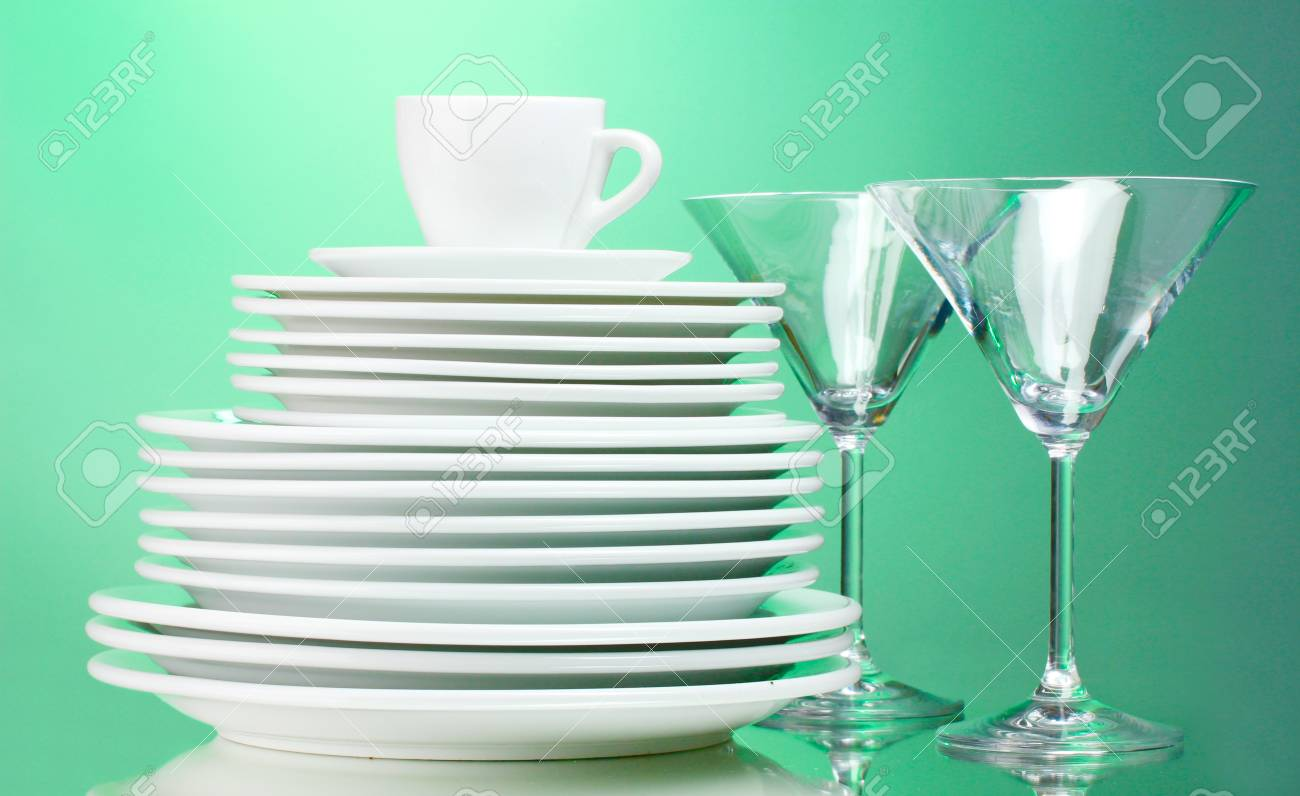 Clean plates, cup and glasses on green background Stock Photo - 11975636