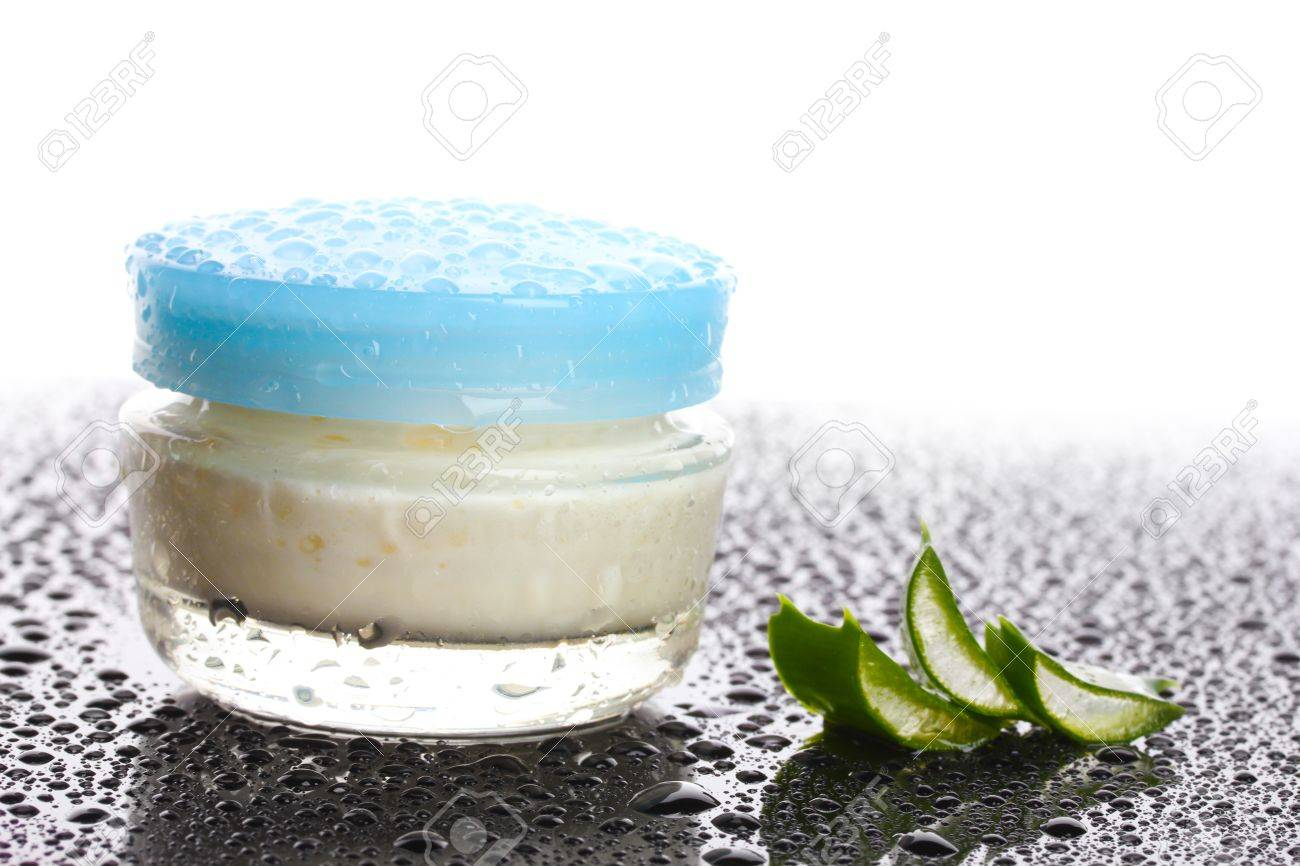 Closed glass jar of cream and aloe on black table with water droplets isolated on white Stock Photo - 12118178