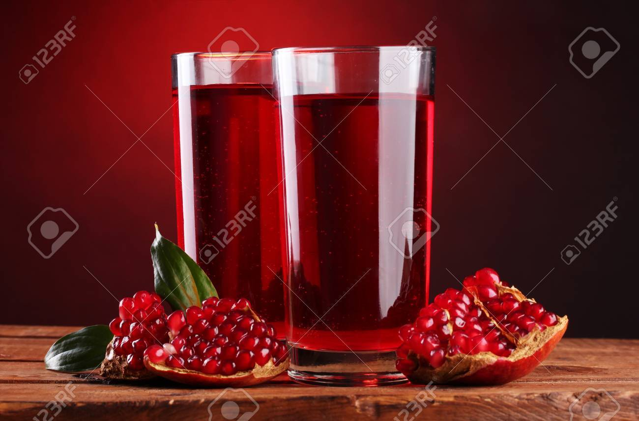 ripe pomergranate and glasses of juice on wooden table on red background Stock Photo - 12144577