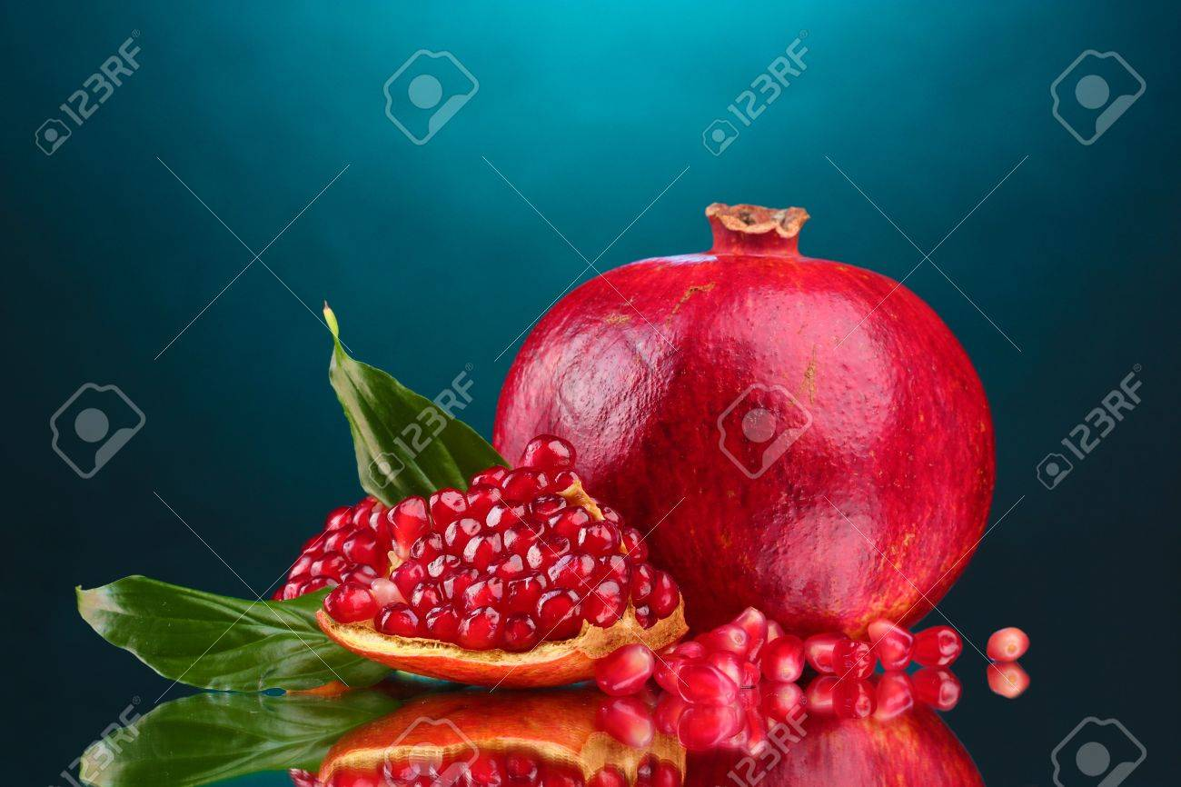 ripe pomegranate fruit with leaves on blue background Stock Photo - 12237140